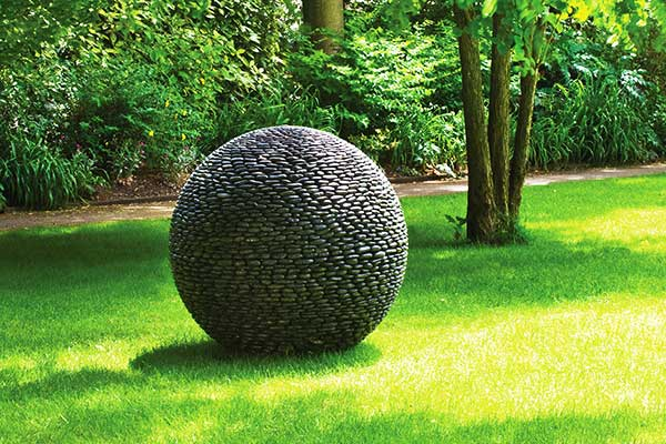 Dark planet garden sculpture on show at Eaton Square Gardens, central London