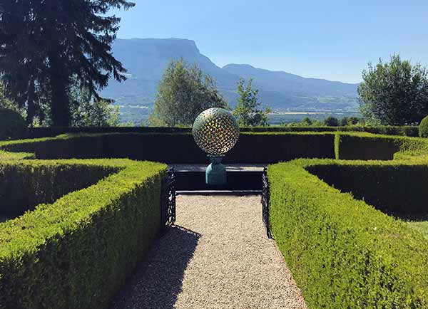 Mantle bronze sphere in the formal garden of a French chateau