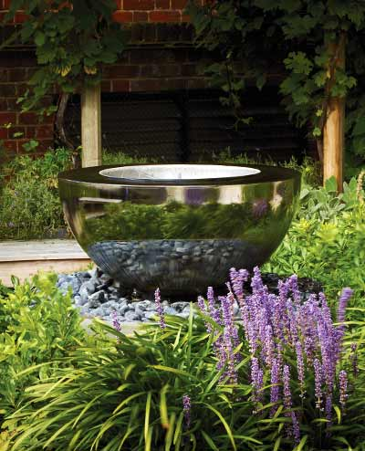 Chalice stainless steel water feature in garden setting