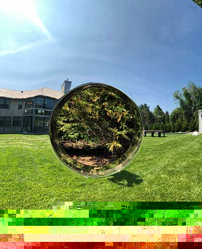 Reflections of the Hamptons Holiday House in the mirror polished surface of the Torus sculpture