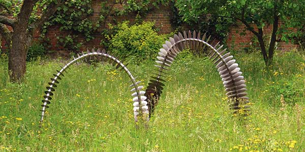Coluna contemporary copper garden art shaped like a snake in grass
