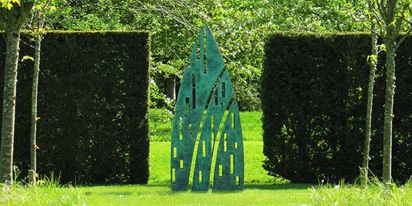 Eveque sculpture as a garden feature in the break between two hedges