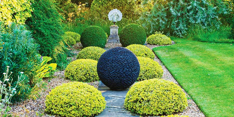 Dark Planet stone sphere in a garden