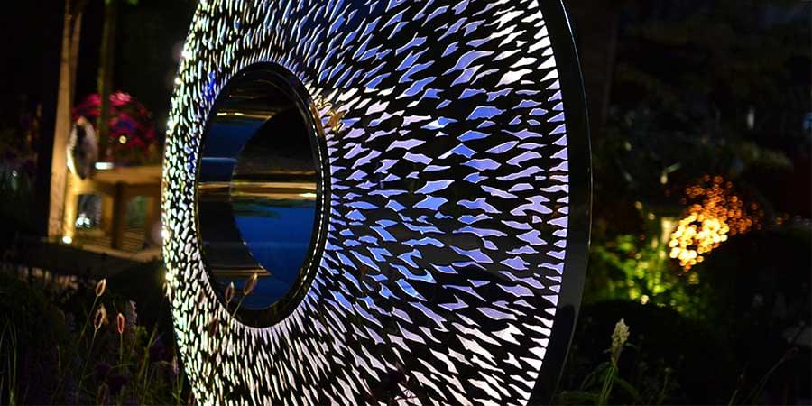 Iris Torus garden sculpture lit up at night
