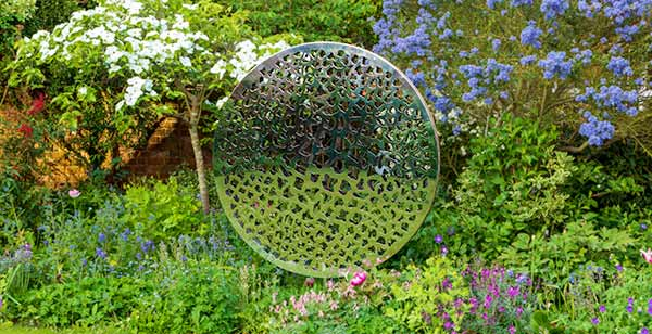 Sculpture made from two parallel circular discs with laser cut patterns that plays with light and shade