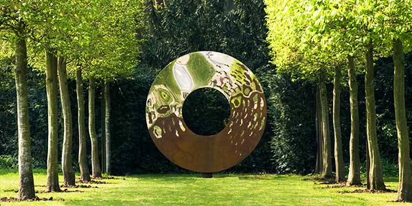 Portal sculpture made from interwoven oxidized and stainless steel as the focal point of a tree avenue
