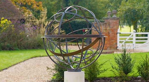 Brass armillary sphere in English country garden