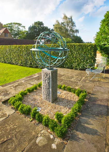 Bronze armillary sphere half hidden by a cloud of lavender