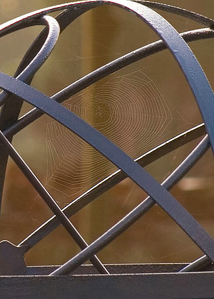 Spiders web spun over the rods of a brass armillary sphere