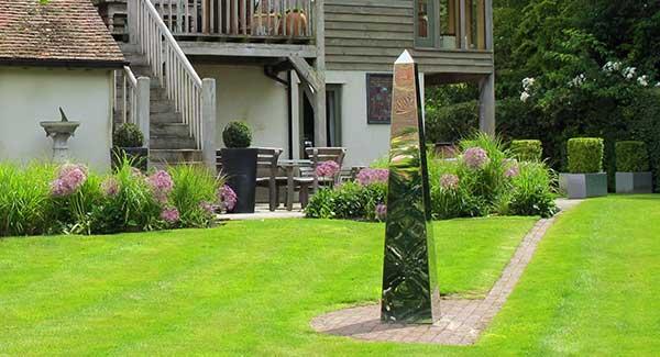 Stainless Steel Obelisk In Classic Garden