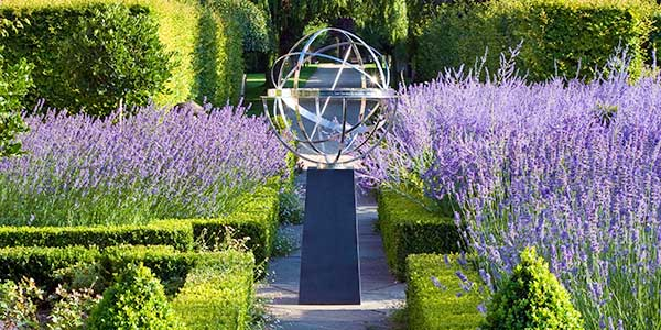 Stainless steel armillary sphere in a landscaped garden