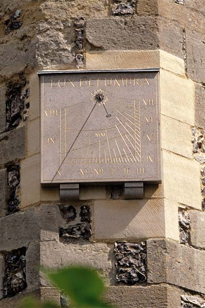 Wall sundial made of stone, complementing the host building
