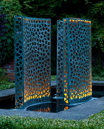 Three verdigris bronze Lattice waterfall walls illuminated at night