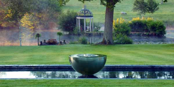 Chalice contemporary stainless steel water feature in a traditional garden